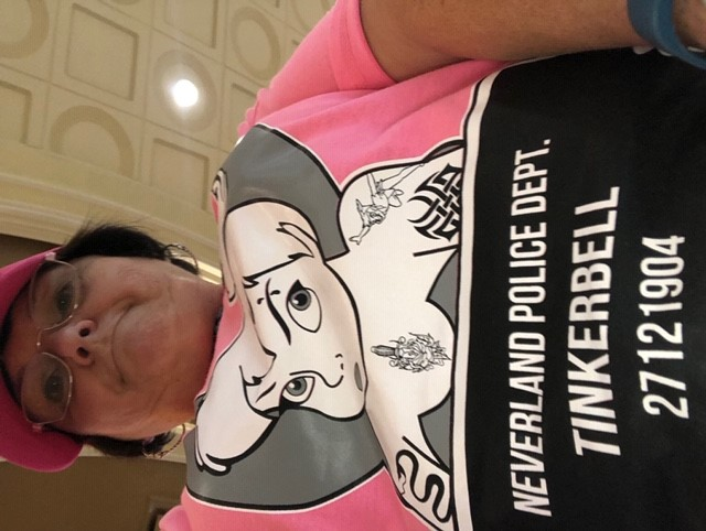 up close picture of Terri in shirt showing a tattooed Tink mug shot for drunk and disorderly conduct